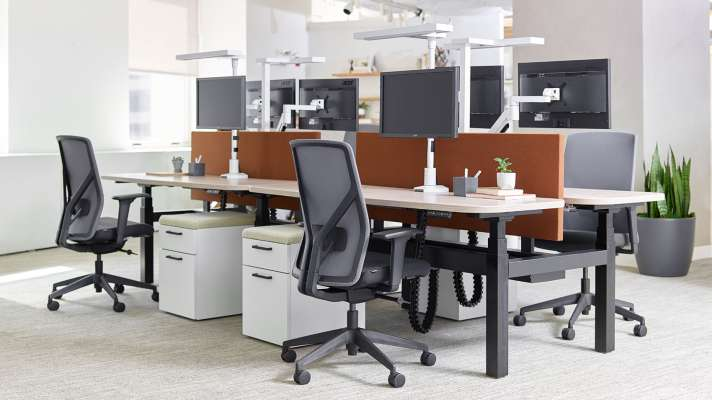 adjustable height desks with synchronized monitor and lighting attachments
